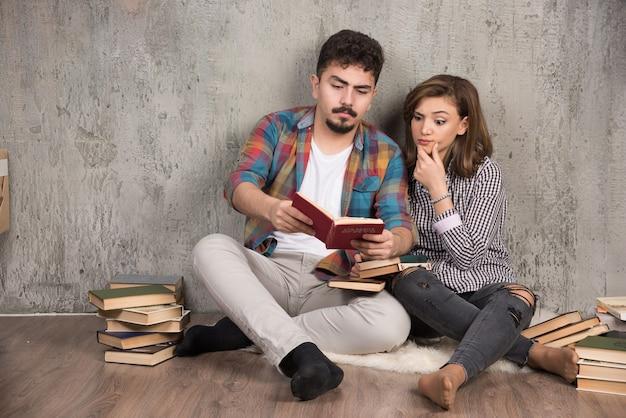 Coppia adorabile che legge un libro interessante mentre era seduto sul pavimento