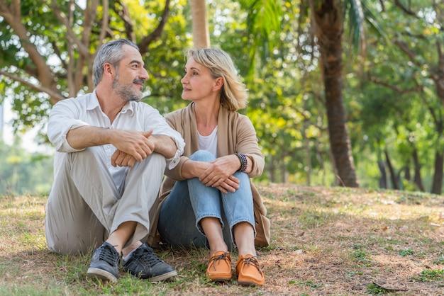 사랑스러운 커플 노인은 함께 공원에 앉아 서로를 봅니다. 노인 은퇴 휴식 개념