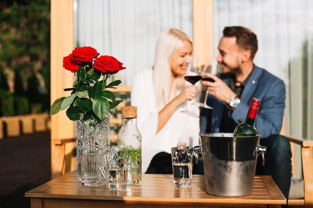 얼음 양동이에 빨간 장미 꽃병과 와인 병 뒤에 앉아 사랑스러운 커플