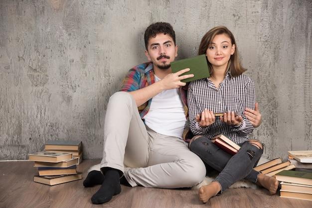 床に座って本を持っている素敵なカップル