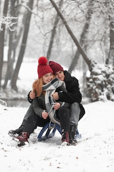 Lovely couple sitting on sleigh