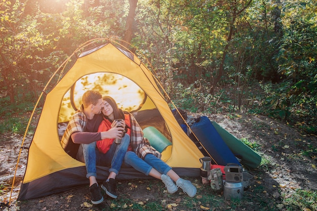 Lovely couple sitting in tent. she leans to him and keep eyes closed. her shoulders are covered with blanket. bearded guy embrace young woman. they hold cups.