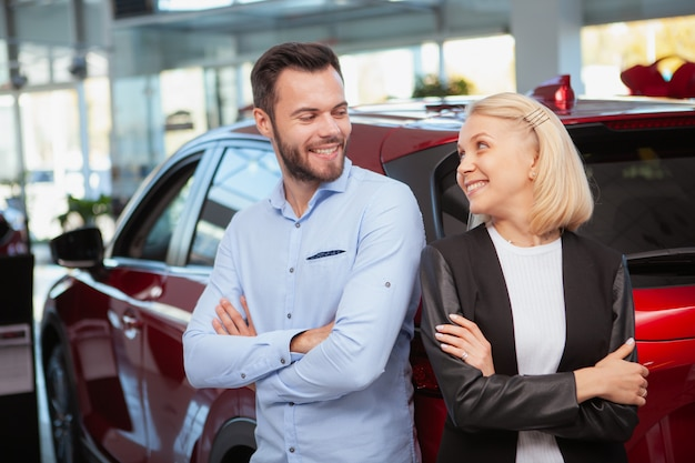 Lovely couple smiling at each other cheerfully, standing near their new car at the dealership