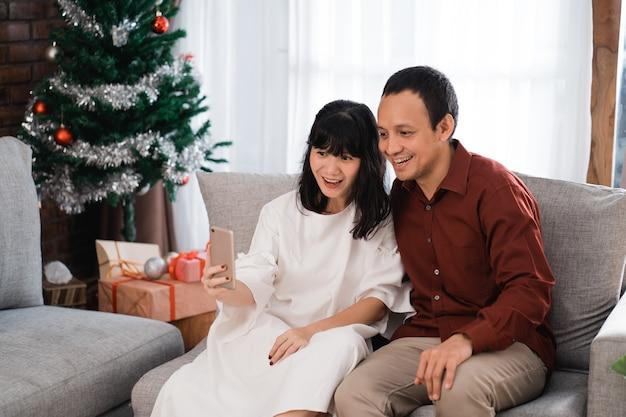 Прекрасная пара, делающая селфи с помощью смартфона в рождественский день