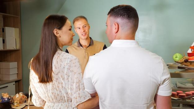 素敵なカップルが居心地の良い装飾が施された菓子店のカウンターに立っている笑顔のバーテンダーと話します、背面図