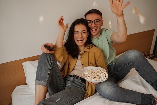 Прекрасная пара бросает поп-конр во время просмотра фильма по телевизору, сидя на кровати. счастливая молодая семья переехала в новую квартиру.