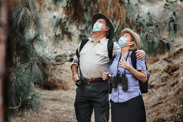 素敵なカップルがマスクを着用して旅行し、covid-19から身を守ります