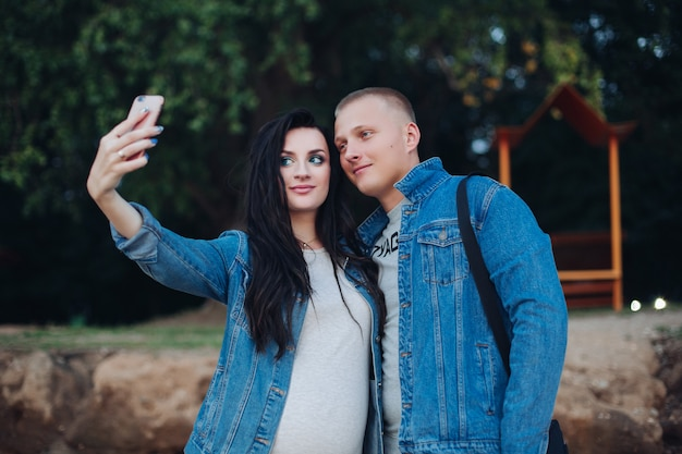 Lovely couple walking in park and taking selfie together