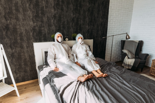 Lovely couple in white protective costumes with hoods and face masks at home on the bed