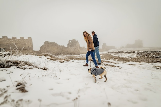 Lovely couple in the winter field on a walk with the dog. dog walking with owner outdoor snowy nature.