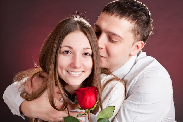 Lovely couple with red rose in the studio. a man anda woman are waiting st. valentine day.