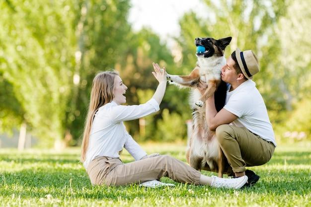 Прекрасная пара с собакой веселятся в парке