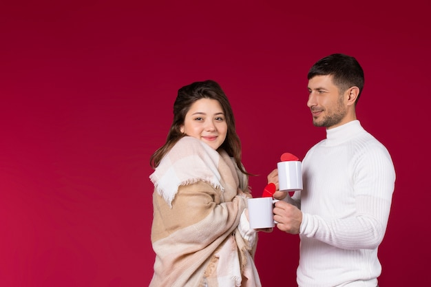 Lovely couple with a warm blanket and white cups of tea on red background.
