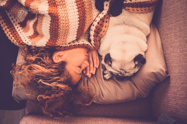 Lovely couple woman pug dog sleep together at home in a tender and sweet romantic scene. staying closer with love and friendship. true relationship between people and animals