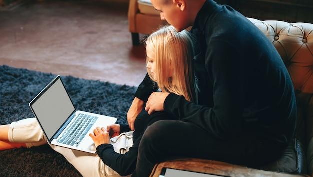 コンピューターを使って自宅で仕事をし、リビングルームで抱き合っている素敵なカップル