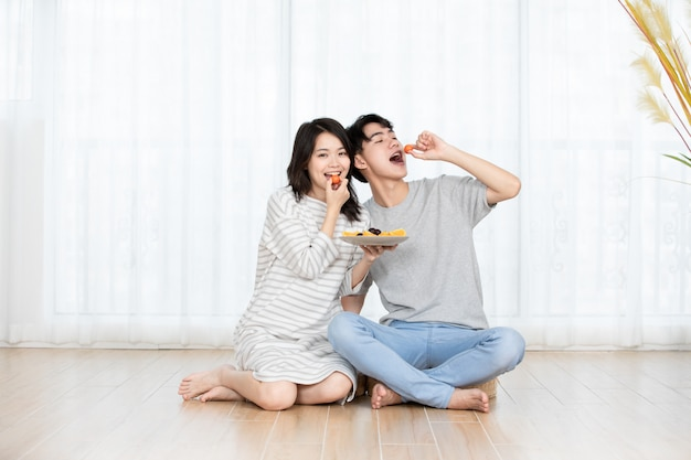 Lovely couples eat fruit at home.