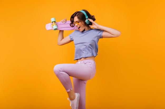 Симпатичная кудрявая девушка в розовых штанах прыгает во время прослушивания музыки. крытое фото радостной кавказской дамы в наушниках, танцующей со скейтбордом.