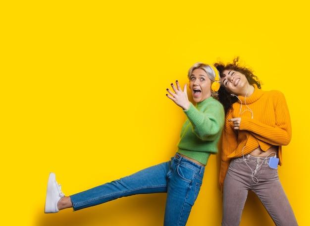 사랑스러운 곱슬 머리 백인 갈색 머리와 그녀의 금발 친구가 음악을 들으면서 여유 공간이있는 노란색 벽에 춤을