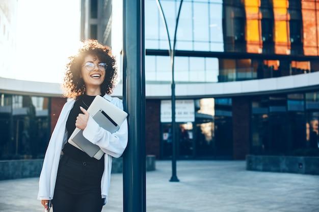 Симпатичный кудрявый предприниматель в очках улыбается на улице, позирует с ноутбуком и планшетом