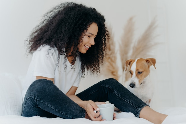 Lovely curly haired female dog owner looks with smile at animal holds cup of tea sits on bed in white spacious bedroom
