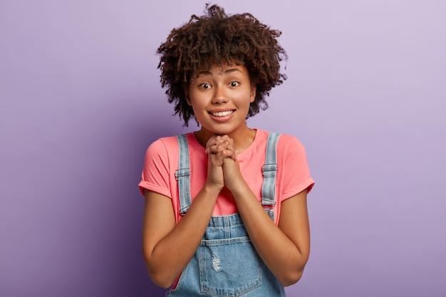 Bella ragazza dai capelli ricci con aspetto angelico, tiene le mani unite, implora favore o aiuto
