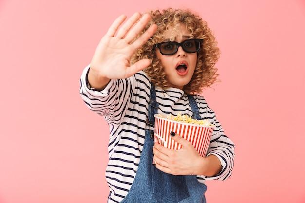 Милая кудрявая женщина 20 лет держит ведро попкорна стоя