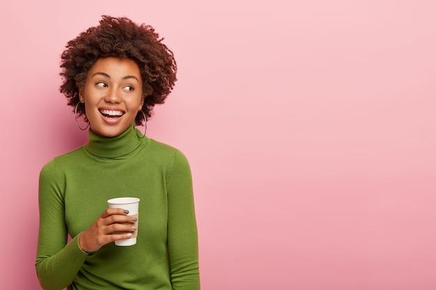 素敵な巻き毛の女性は持ち帰り用のコーヒーを持って、休憩を楽しんで、緑のタートルネックのジャンパーを着て、右側を見て、ピンクの壁にポーズをとって、あなたの広告コンテンツのための空きスペース