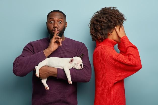 素敵な巻き毛の女性が立ち上がって目を覆い、夫からの驚きを待ちます。浅黒い肌の男は沈黙のジェスチャーをし、彼が何を提示しようとしているのかわからないように頼み、小さな眠っている犬を抱き、贈り物をします