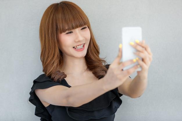 幸せそうな顔のスマートフォンで自分撮り写真を作る素敵なかわいいアジアの女の子、テクノロジーでティーンと現代の人々のライフスタイルのコンセプト。