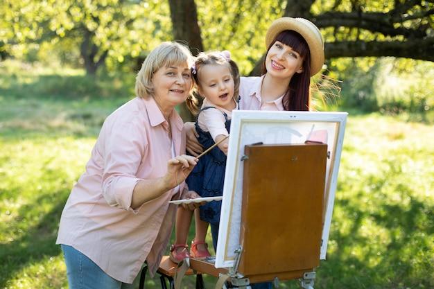 Милая девочка дошкольного возраста, наслаждаясь рисованием со своей мамой и бабушкой на открытом воздухе в красивом летнем саду в солнечный день. рисование картины на холсте красками.