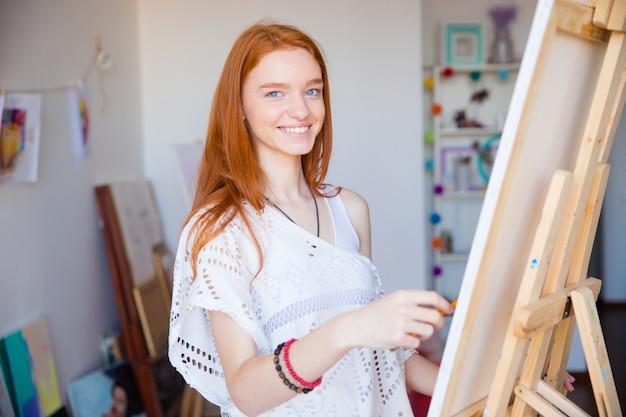 예술 워크샵에서 그림을 즐기는 사랑스러운 귀여운 즐거운 젊은 빨간 머리 여자 아티스트