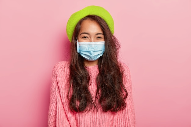 Милая темноволосая азиатка болеет эпидемией, носит защитную медицинскую маску, зеленый берет и свитер.