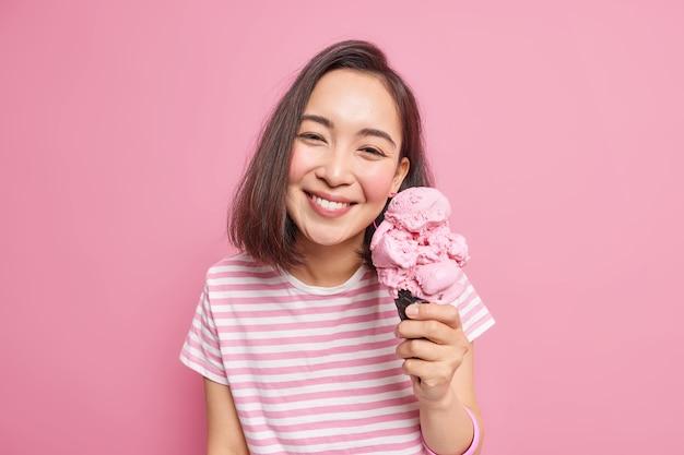 Милая темноволосая азиатская женщина любит есть вкусное клубничное мороженое в жаркий летний день, у нее приподнятое настроение, довольное выражение лица, одетая небрежно, позирует с любимым замороженным десертом в помещении