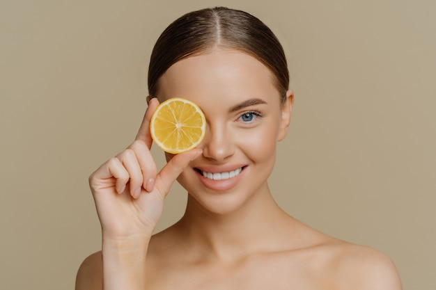 Lovely dark haired european woman smiles gently covers eye with slice of juicy lemon poses half naked