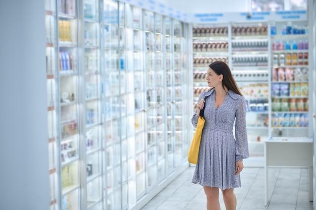 다른 의약품으로 약국 진열장을 쳐다보고 있는 사랑스러운 검은 머리의 백인 중년 여성