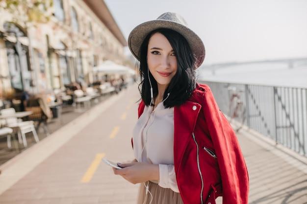 Милая темноволосая женщина в шляпе слушает музыку возле летнего кафе