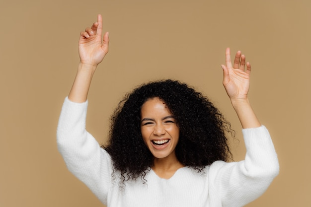 Lovely dark skinned female model has toothy smile, raises hands, points up, feels overjoyed