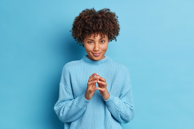 Lovely dark skinned female model looks mysteriously at camera has tricky expression while scheming something and steepling fingers makes plans stands indoor at studio wears casual blue sweater