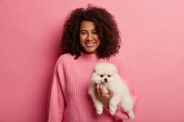 Lovely dark skinned lady in knitted sweater, being friendly companion to dog, wears pink sweater
