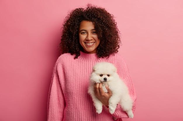Adorabile signora dalla pelle scura in maglione lavorato a maglia, essendo un compagno amichevole per il cane, indossa un maglione rosa