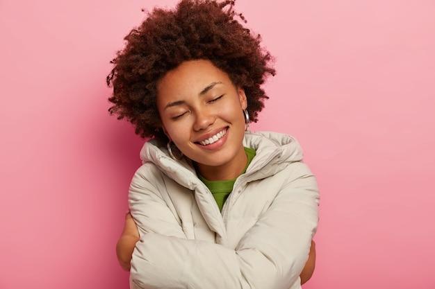 사랑스러운 어두운 피부의 여성이 자신을 포용하고 새로운 겨울 코트에서 편안함을 즐깁니다.