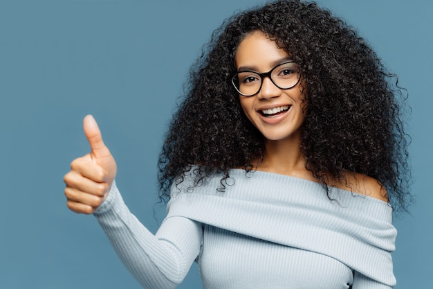 Lovely dark skinned woman gives thumb up, wears fashionable sweater, eyewear, demonstrates approval