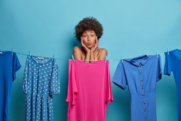 素敵な黒い肌の女性は唇を丸く保ち、キスをしたい、服を選ぶ、特別な機会にドレスを着る、洗ったドレスを着たロープ。服のコレクション。女性は着る服装を選択します