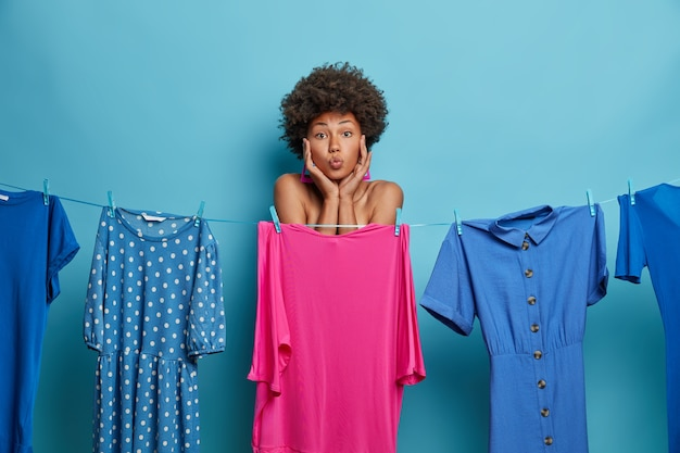 Lovely dark skinned woman keeps lips rounded, wants kiss, chooses outfit, dresses on special occasion, rope with washed dresses. collection of clothes. lady selects attire to wear