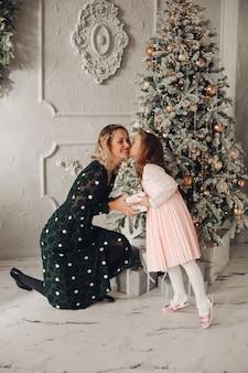 彼女の母親にキスするピンクのドレスを着た素敵な娘