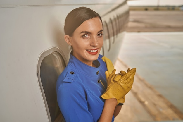Lovely day in the airport of a smiling stewardess standing with her back towards the aircraft