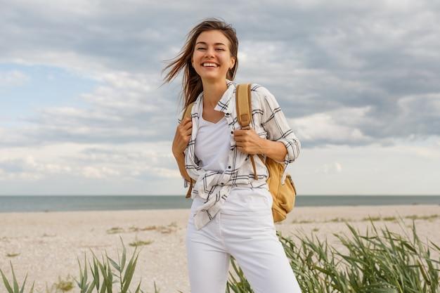 Симпатичная жизнерадостная путешествующая женщина брюнет с рюкзаком, наслаждаясь праздниками.