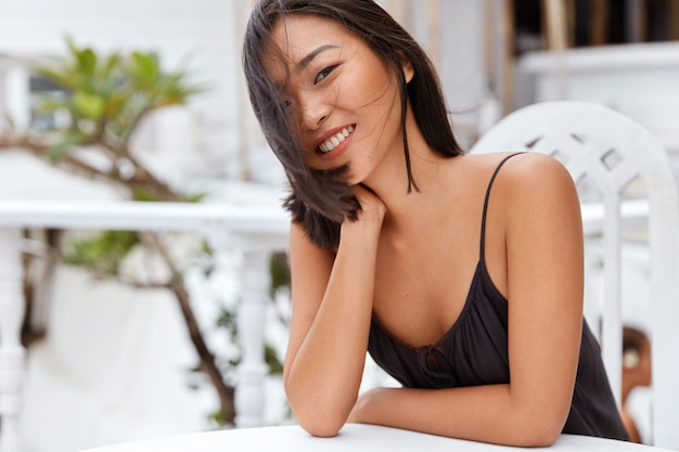 Lovely delighted chinese woman with bobbed hairstyle and pleasant appearance, happy to spend recreation time in cozy terrace cafe, going to taste local cuisine as being in unknown exotic place