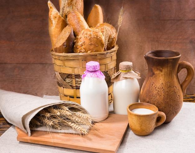 牛乳のボトルと木製の水差しの横にあるリネンで包まれた織りバスケットとかすかな穀物のカントリーパンの素敵な展示