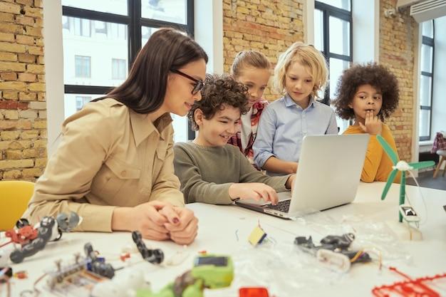 Милые разноплановые дети улыбаются, наблюдая за видео о научной робототехнике, сидя за столом в